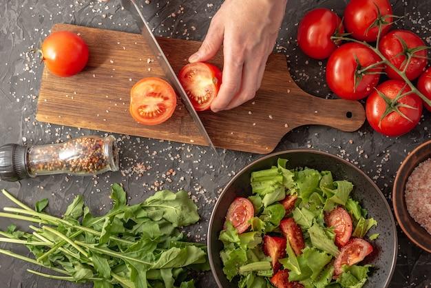 As mãos das mulheres estão cortando um tomate maduro para cozinhar uma salada de legumes com tomates e rúcula