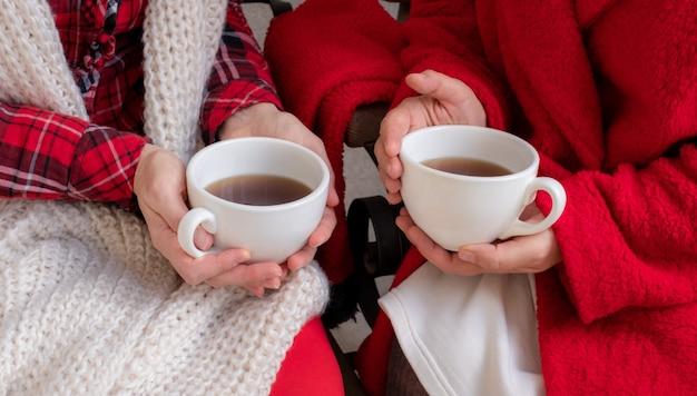 As mãos das mulheres estão segurando uma xícara branca de chá ou café, vestidas com roupas festivas vermelhas e brancas