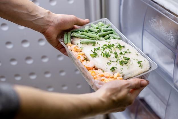 As mãos das mulheres estão tirando um recipiente com um prato congelado do freezer da geladeira