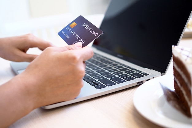 As mãos das mulheres estão usando computadores e cartões de crédito para encomendar produtos on-line.