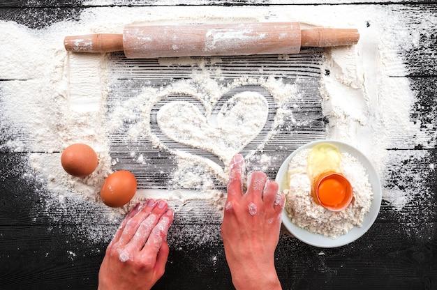 As mãos das mulheres estender a massa sobre uma mesa preta polvilhada com farinha.