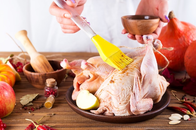 As mãos das mulheres mancham a galinha crua, fresca do molho em uma tabela de madeira. cozinha passo-a-passo