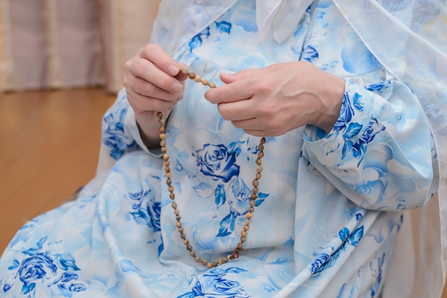 As mãos das mulheres muçulmanas com seus rosários