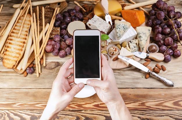 As mãos das mulheres no smartphone tirar fotos de comida