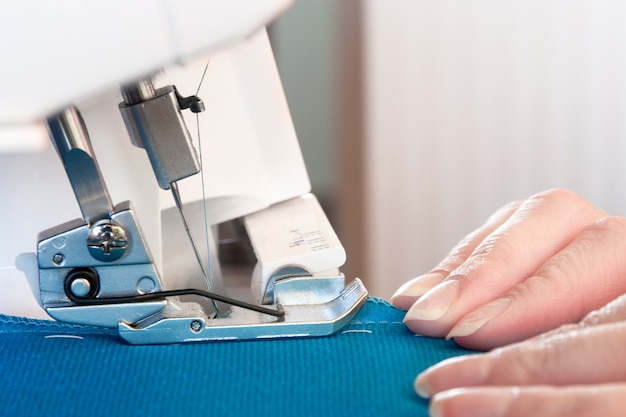 As mãos das mulheres no trabalho na máquina de costura.