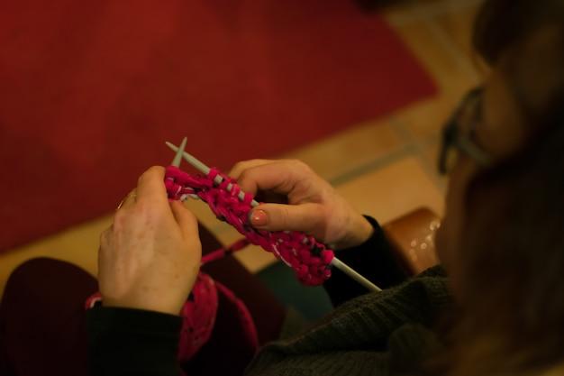 As mãos das mulheres que fazem o crochet em um sofá.