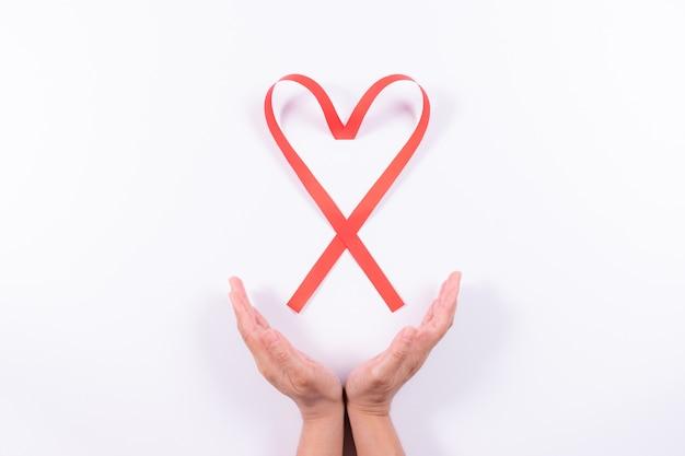 As mãos das mulheres são gentilmente abraçadas fita vermelha