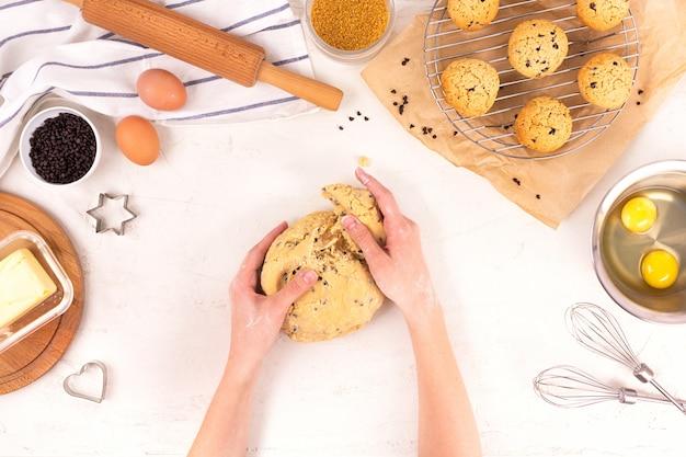 As mãos das mulheres seguram a massa para fazer biscoitos. equipamentos culinários e ingredientes. ovos, farinha, açúcar, chocolate, manteiga, bakeware. lay plana.