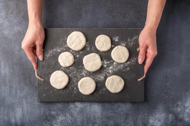 As mãos das mulheres seguram bolos de queijo semiacabados em uma tábua de corte de ardósia escura sobre um fundo de madeira