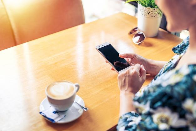 As mãos das mulheres seguram o telefone móvel com o conteúdo da mensagem de texto da tela da cópia do espaço da cópia em branco