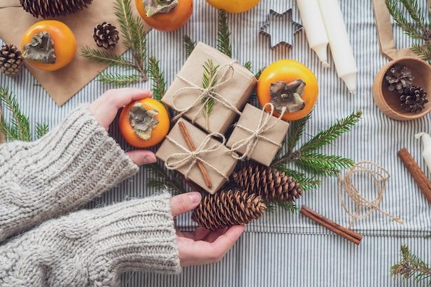 As mãos das mulheres seguram presentes para o ano novo. fundo de natal com caixas de presente, cones, árvore de natal e caqui, vista superior, close-up. feito à mão presente.