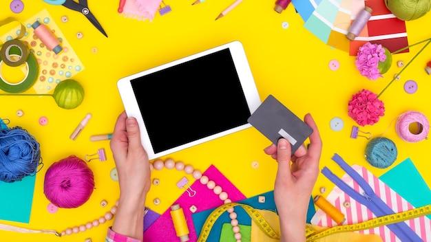 As mãos das mulheres seguram um cartão de crédito e fazem compras online em um tablet. local de trabalho diy com equipamento artesanal em fundo amarelo. brincar.