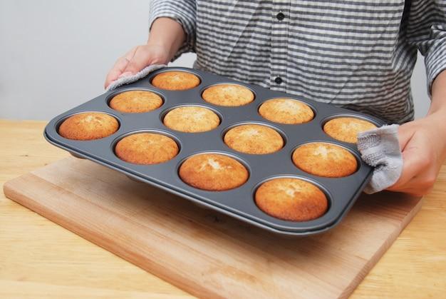 As mãos das mulheres segurando o molde de metal com muffins.