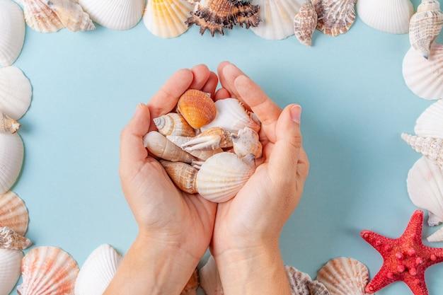 As mãos das mulheres segurar conchas sobre um fundo azul de verão com diferentes conchas e estrelas do mar