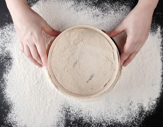 As mãos das mulheres segurar uma peneira de madeira redonda e peneirar a farinha de trigo branca