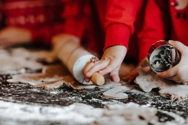 As mãos das pessoas com roupas de inverno vermelho, fazendo biscoitos na cozinha com fundo de natal.