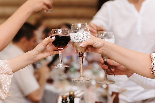 As mãos das pessoas tilintam de copos com bebidas alcoólicas em um feriado em um restaurante
