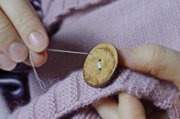 As mãos das trabalhadoras costuram um botão de madeira em uma jaqueta. fechar-se.