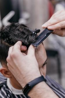 As mãos de barberã cortam o cabelo com uma tesoura, close-up