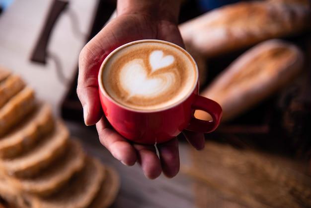 As mãos de barista estão entregando café aos clientes.