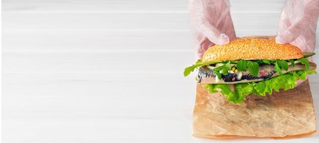 As mãos de cook colocam um sanduíche de filé de arenque com cebola, pepino e salada no papel