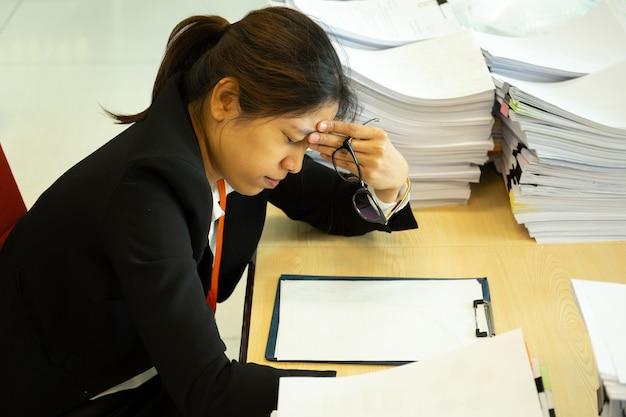 As mãos de descanso da mulher de negócios na cabeça com olhos fecham-se na mesa do trabalho no escritório.