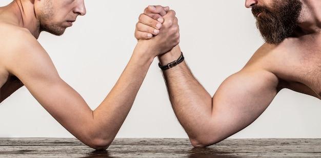 As mãos de dois homens se cruzaram em uma queda de braço, forte e fraca, combinação desigual. homem barbudo fortemente musculoso lutando contra um homem fraco e franzino. braços lutando com a mão magra, braço grande e forte em estúdio.