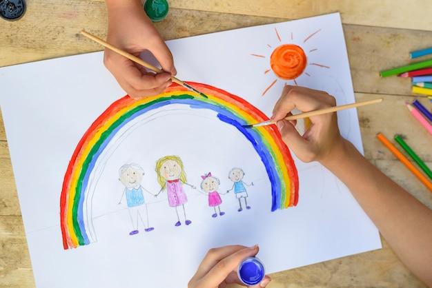 As mãos de duas crianças fazem um desenho com um pincel e tintas. vista do topo