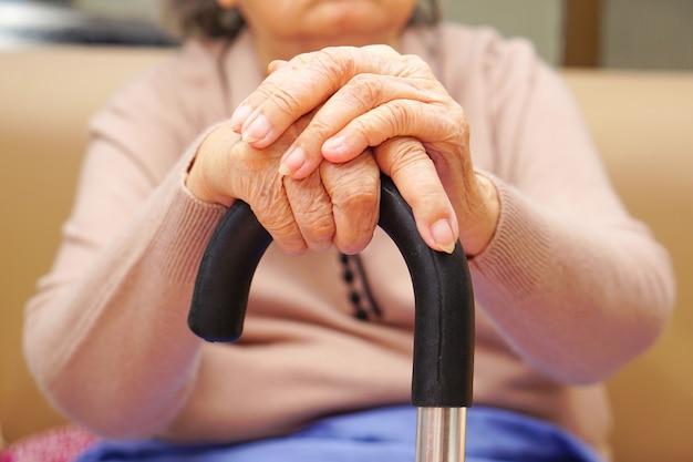 As mãos de idosa idosa ou sênior asiática com sardas e enrugadas nas mãos usam as mãos segurando uma bengala na frente de si mesmo. conceito de saúde e médico.