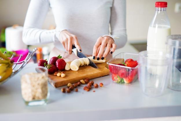 As mãos de menina bonita jovem estão cortando bananas e morangos no balcão da cozinha, preparando-os para um smoothie.