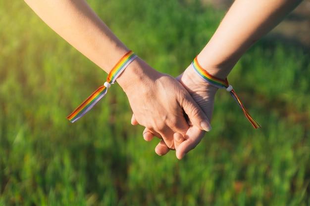 As mãos de meninas lésbicas entrelaçadas com pulseiras de arco-íris na parede de grama verde desfocada ao pôr do sol
