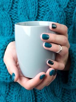 As mãos de mulher com manicure turquesa segurar uma xícara cinza de café ou chá