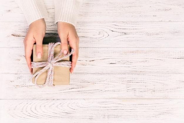As mãos de mulher dão namorados embrulhados ou outro presente artesanal de férias em papel com fita rosa. caixa de presente, decoração de presente na mesa de madeira branca, vista superior com copyspace