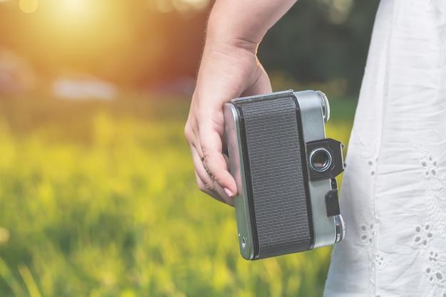 As mãos de mulher estão segurando a câmera antiga do filme vintage ao ar livre.