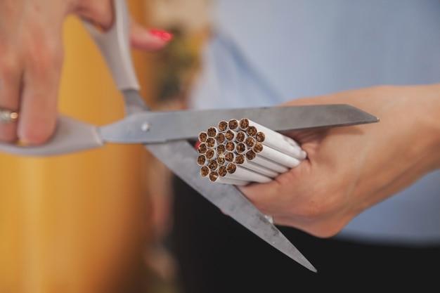As mãos de mulher jovem cortam cigarros com uma tesoura. pare de fumar, lute contra os viciados em nicotina. close-up de um monte de cigarro de corte de tesoura. conceito de anti-tabagismo e estilo de vida saudável. copie o espaço