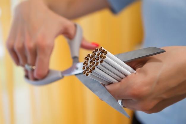 As mãos de mulher jovem cortam cigarros com uma tesoura. pare de fumar, lute contra os viciados em nicotina.