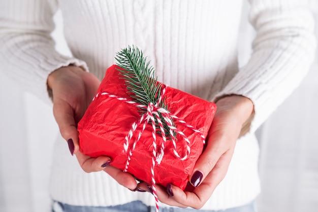 As mãos de mulher segura a caixa de presente de natal.