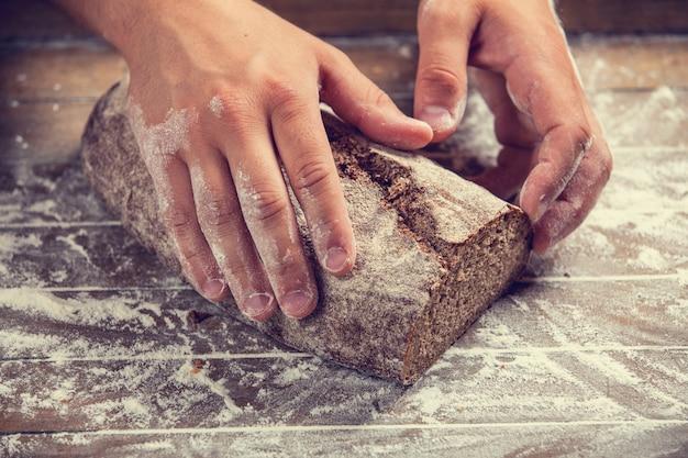 As mãos de padeiro com um pão. foto com alto contraste