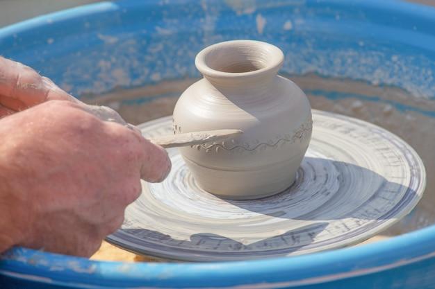 As mãos de potter colocam padrão no jarro na roda de oleiro