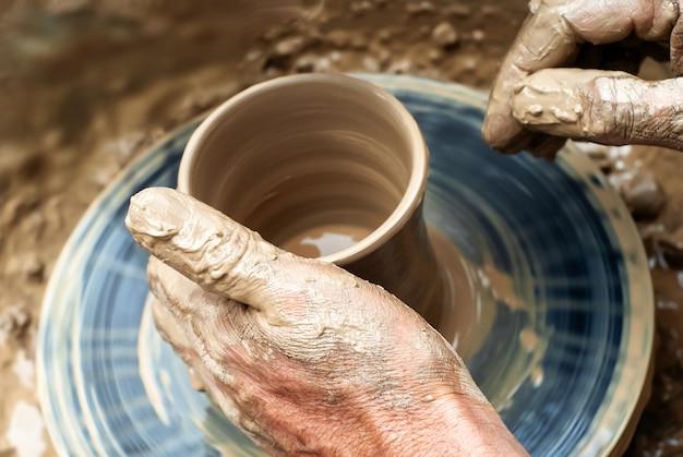 As mãos de potter moldam a cerâmica em uma roda giratória, close-up
