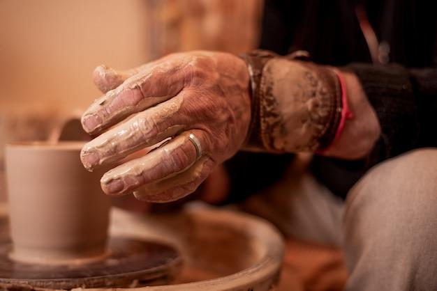 As mãos de potter trabalham com argila, tornando-o um produto