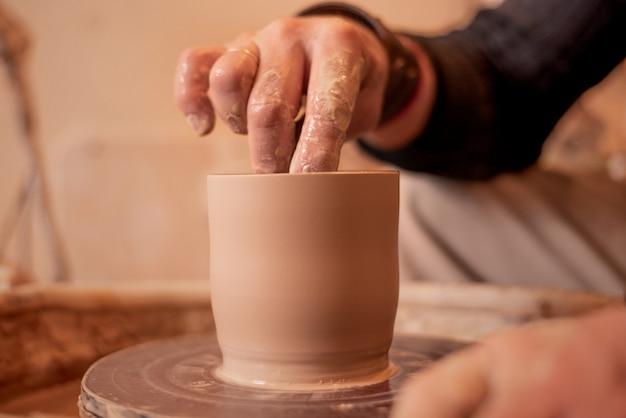 As mãos de potter trabalham com argila, tornando-se um produto