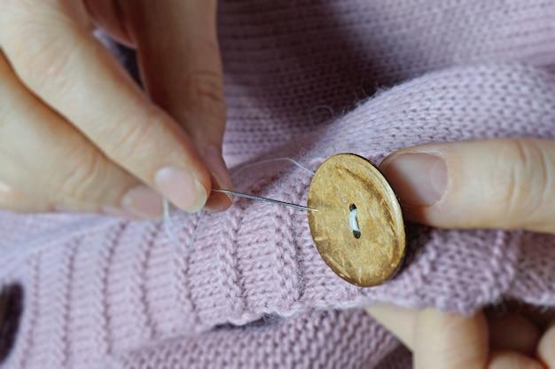 As mãos de trabalhadoras costuram um botão de madeira em uma jaqueta