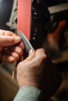 As mãos de um chaveiro afiando a peça de trabalho para uma faca em uma cinta de esmerilar