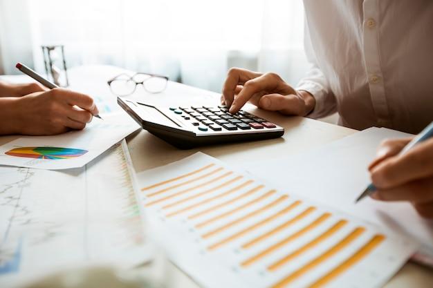 As mãos de um contador preparam um relatório financeiro em uma calculadora.