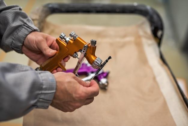 As mãos de um funcionário da oficina pintando e limpando a pistola de pulverização