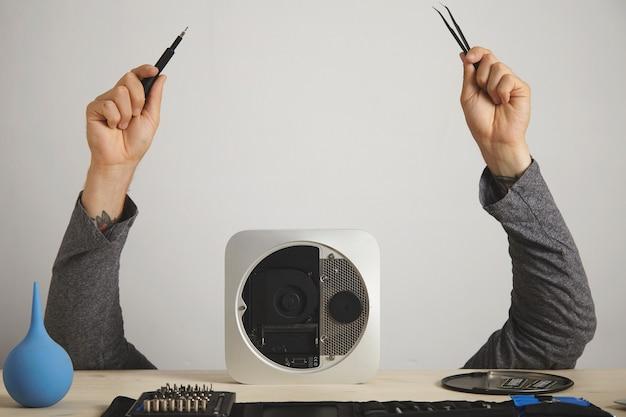As mãos de um homem com pinças e chave de fenda, a cabeça do homem está escondida atrás de um computador, na parede branca