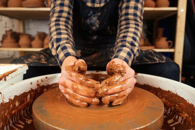 As mãos de um homem de barro na roda de oleiro moldam um vaso. o oleiro trabalha em uma oficina de olaria com barro. o conceito de maestria e criatividade em cerâmica