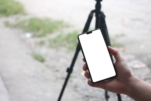 As mãos de um homem de negócios que guardam um smartphone vazio e têm o espaço da cópia.