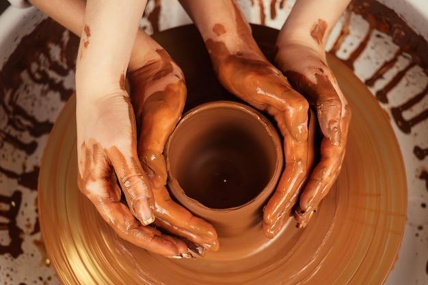As mãos de um homem e de uma mulher em argila em uma roda de oleiro moldam um vaso. o oleiro trabalha em uma oficina de olaria com barro. o conceito de dia dos namorados e o amor na cerâmica